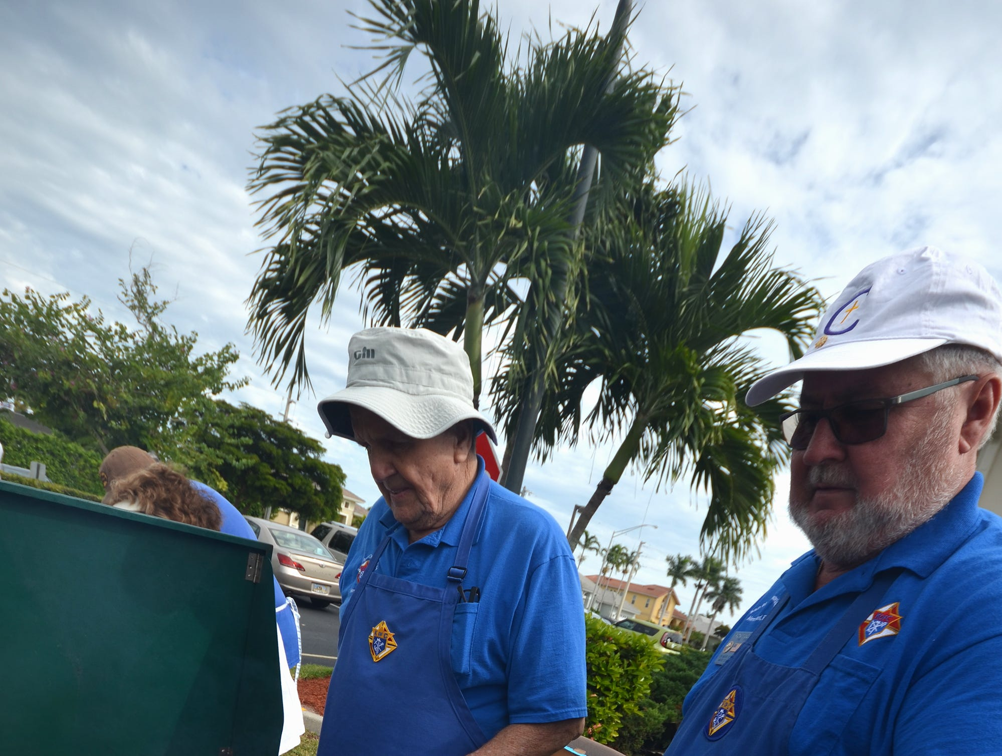 Volunteer chefs Dick Poulanger, left, and Ron McClay man the grill. The Marco Island Knights of Columbus held their inaugural car show Saturday in the parking lot at San Marco Catholic Church.