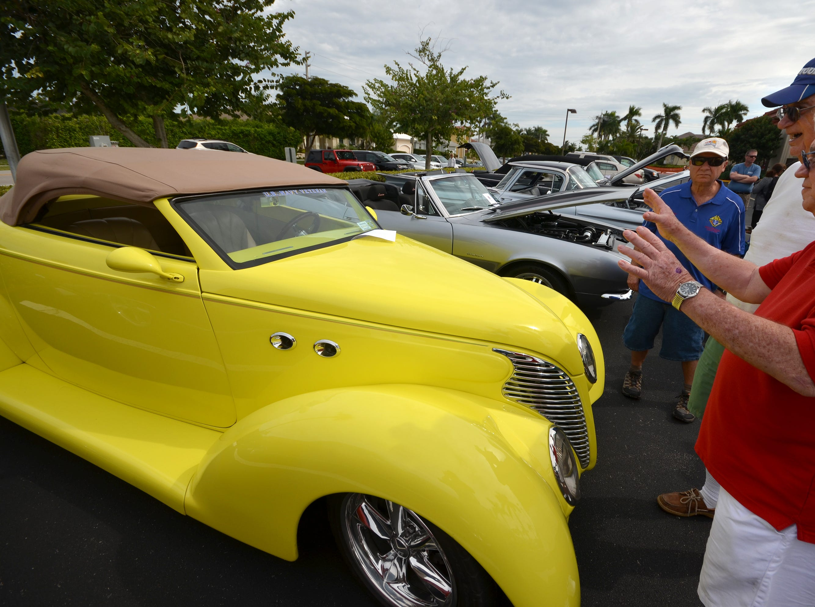 Fans inspect Dick Fracasse's 1939 Ford convertible. The Marco Island Knights of Columbus held their inaugural car show Saturday in the parking lot at San Marco Catholic Church.