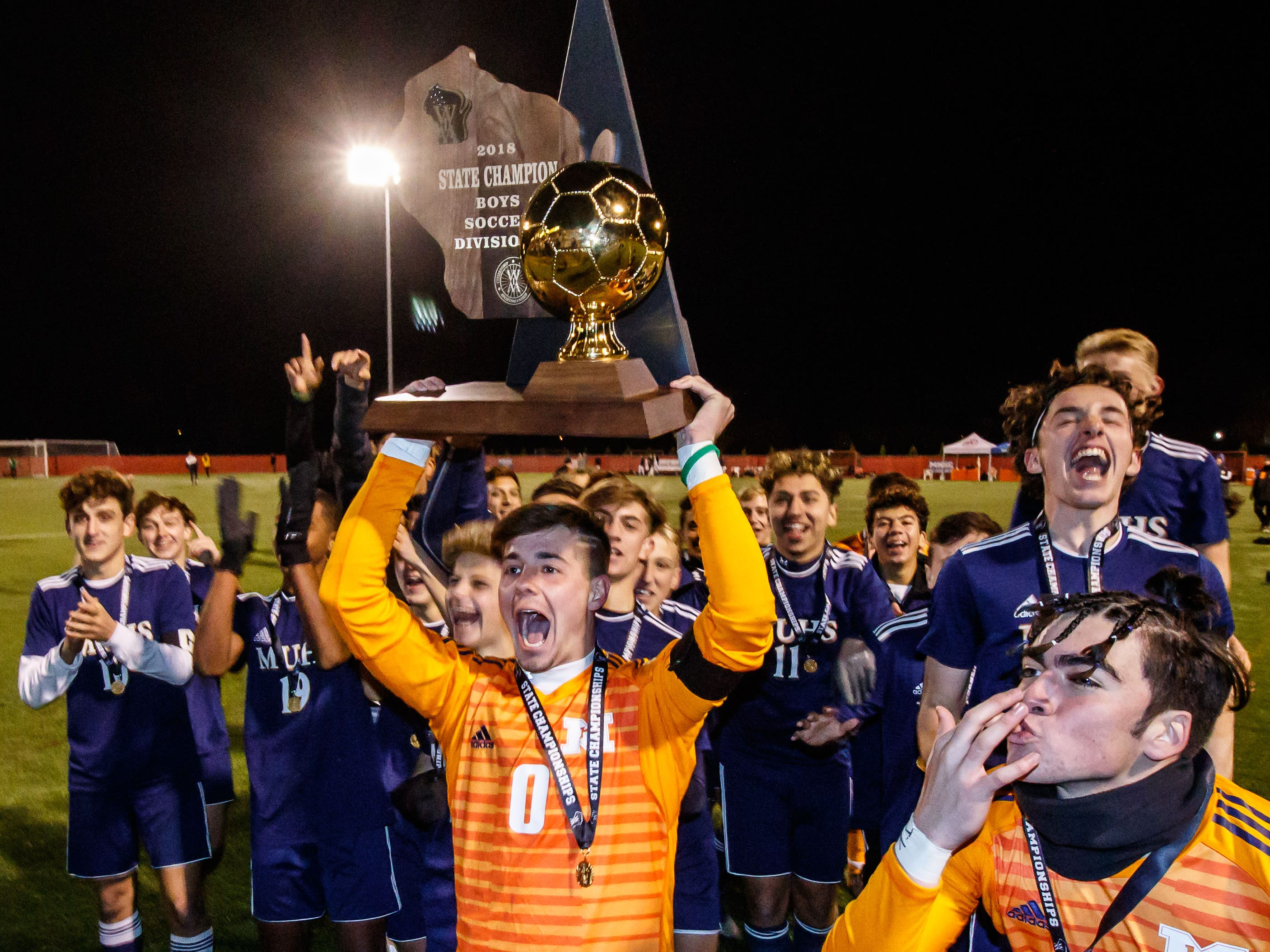 Marquette goalie Carter Abbott (0) hoists the gold ball for the fans after winning the the WIAA Division 1 state soccer title match 3-0 over Hamilton at Uihlein Soccer Park in Milwaukee on Saturday, Nov. 3, 2018.