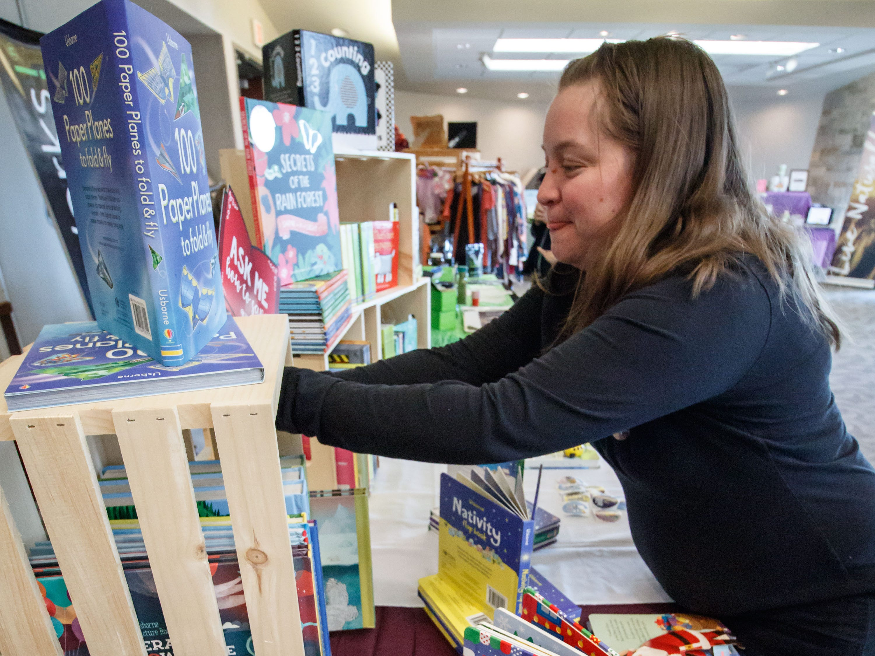 Sandy George of Usborne Books organizes her display during the 2018 Holiday Bazaar at the Menomonee Falls Library on Saturday, Nov. 3. The annual event is a fundraising endeavor for the Friends of the Library, with a percentage of all sales supporting the group.