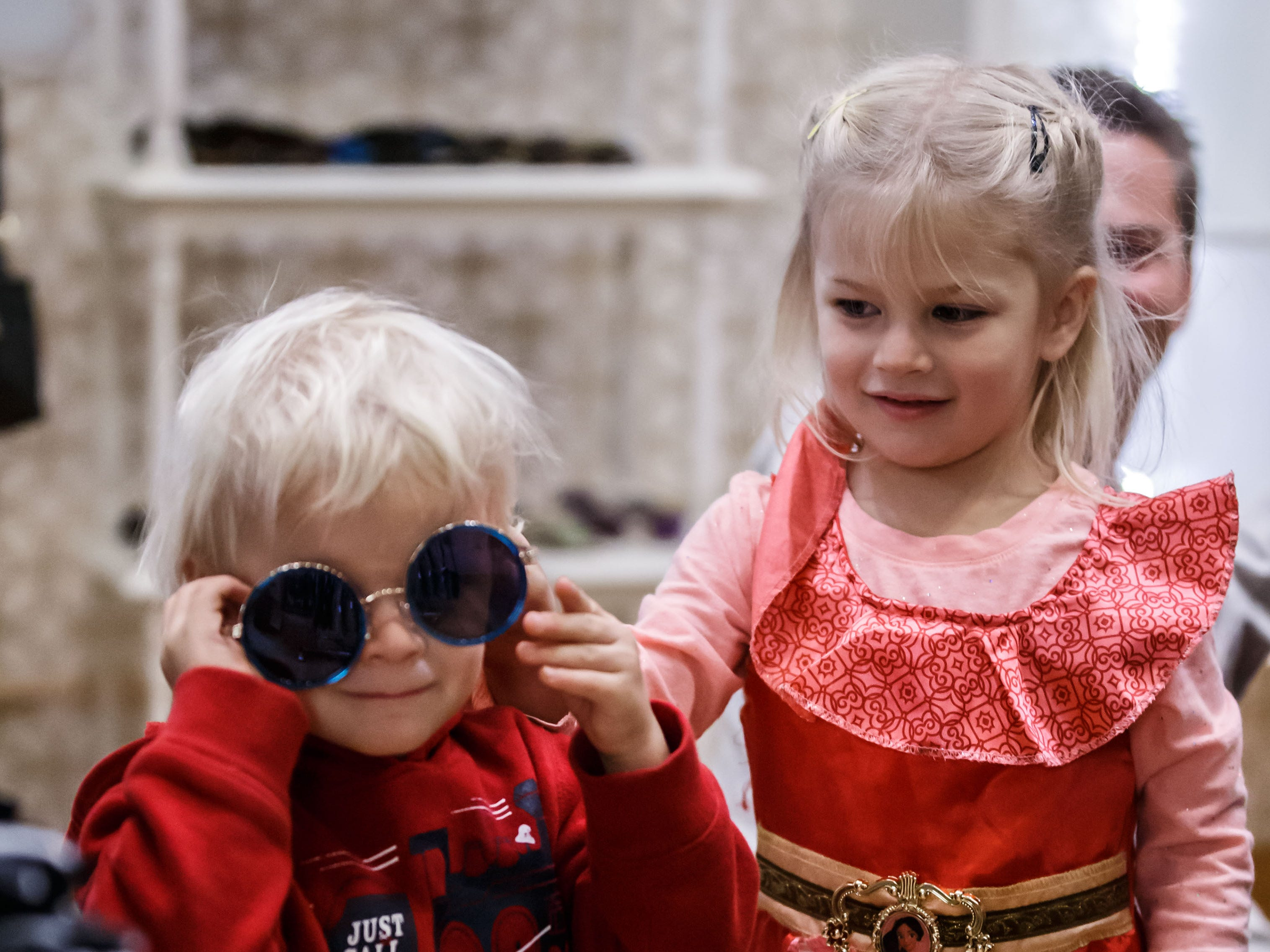 Two-year-old Samuel Stewart of Watertown gets a little help from sister Scarlett, 4, while trying on sun glasses at Bangles & Bags in Oconomowoc during the annual Fall Gallery Night event on Friday, Nov. 2, 2018.