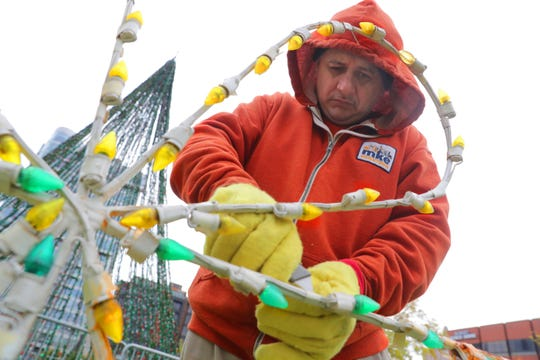 Hector Jaime with Milwaukee Downtown works on getting the holiday lights ready at Cathedral Square Park on East Wells Street in Milwaukee on Nov. 5. The decorations, part of the Milwaukee Holiday Lights Festival, will be lighted through the holiday season. Cathedral Square and Zeidler Union Square also have lights as part of the holiday display.