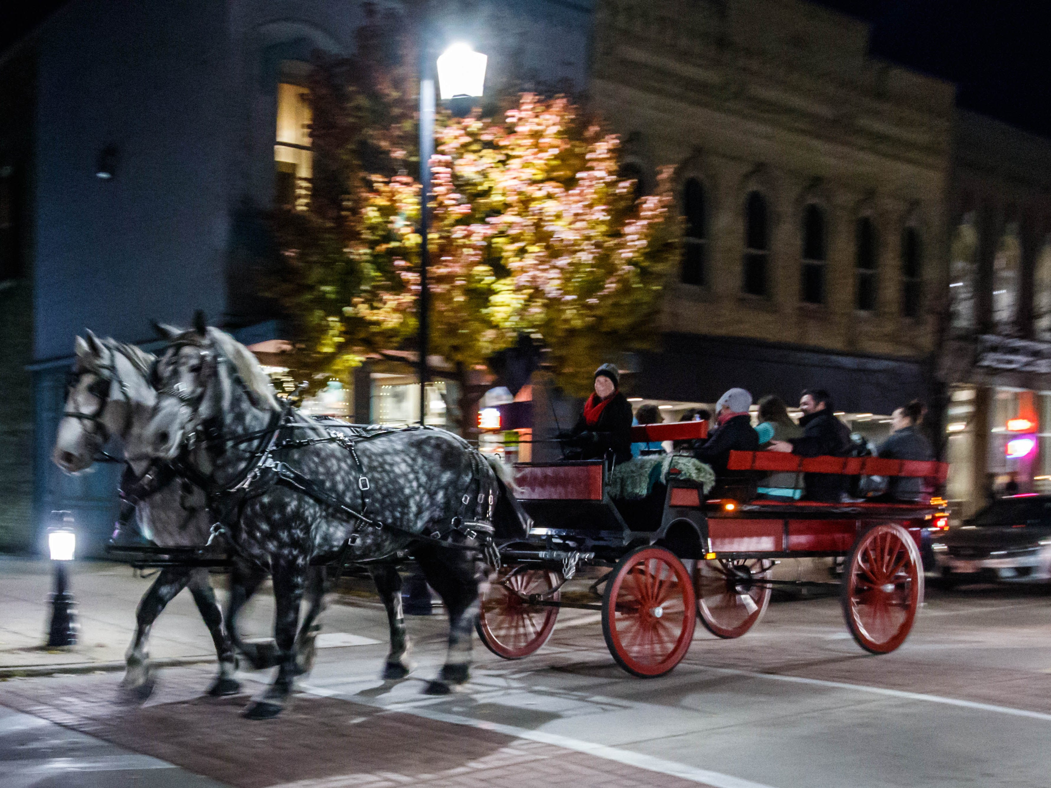 Visitors enjoy a scenic horse-drawn carriage ride from Hoof Beats Express through downtown Oconomowoc during during the annual Fall Gallery Night event on Friday, Nov. 2, 2018. The annual event, hosted by the Downtown Oconomowoc Business Association, features an evening of art, live music, shopping and more.