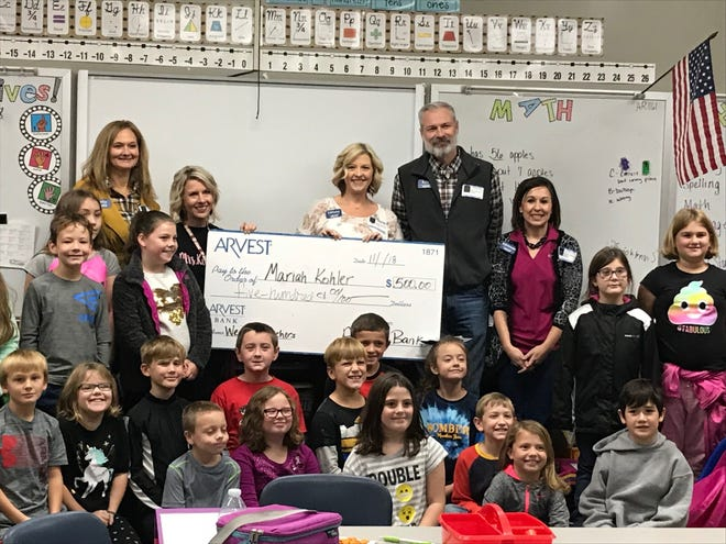 Mariah Kohler, a third-grade teacher at Hackler Intermediate School in Mountain Home, recently received a $500 award from Arvest Bank. Pictured along with Kohler and her students are members of the local Arvest Market.