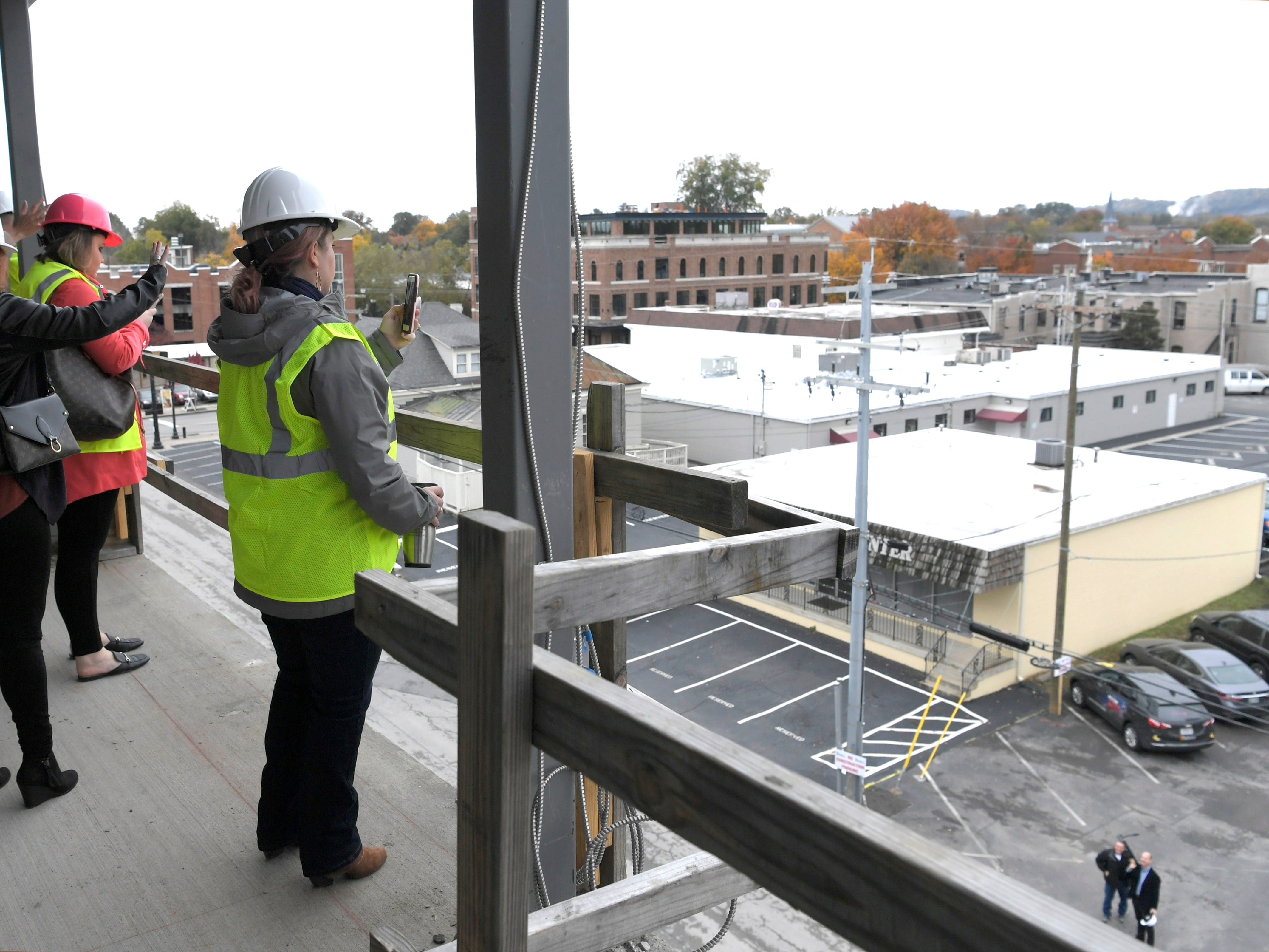 People take photographs of the view of downtown Franklin from a balcony at Harpeth Square during a tour of the construction site on Monday, Nov. 5, 2018.  It's been nearly a year since the $110 million development in downtown Franklin broke ground.   Harpeth Square is featuring a Curio Hilton Hotel with restaurant, 150 apartments, retail/restaurant space with street-level space, and 591-space parking garage.