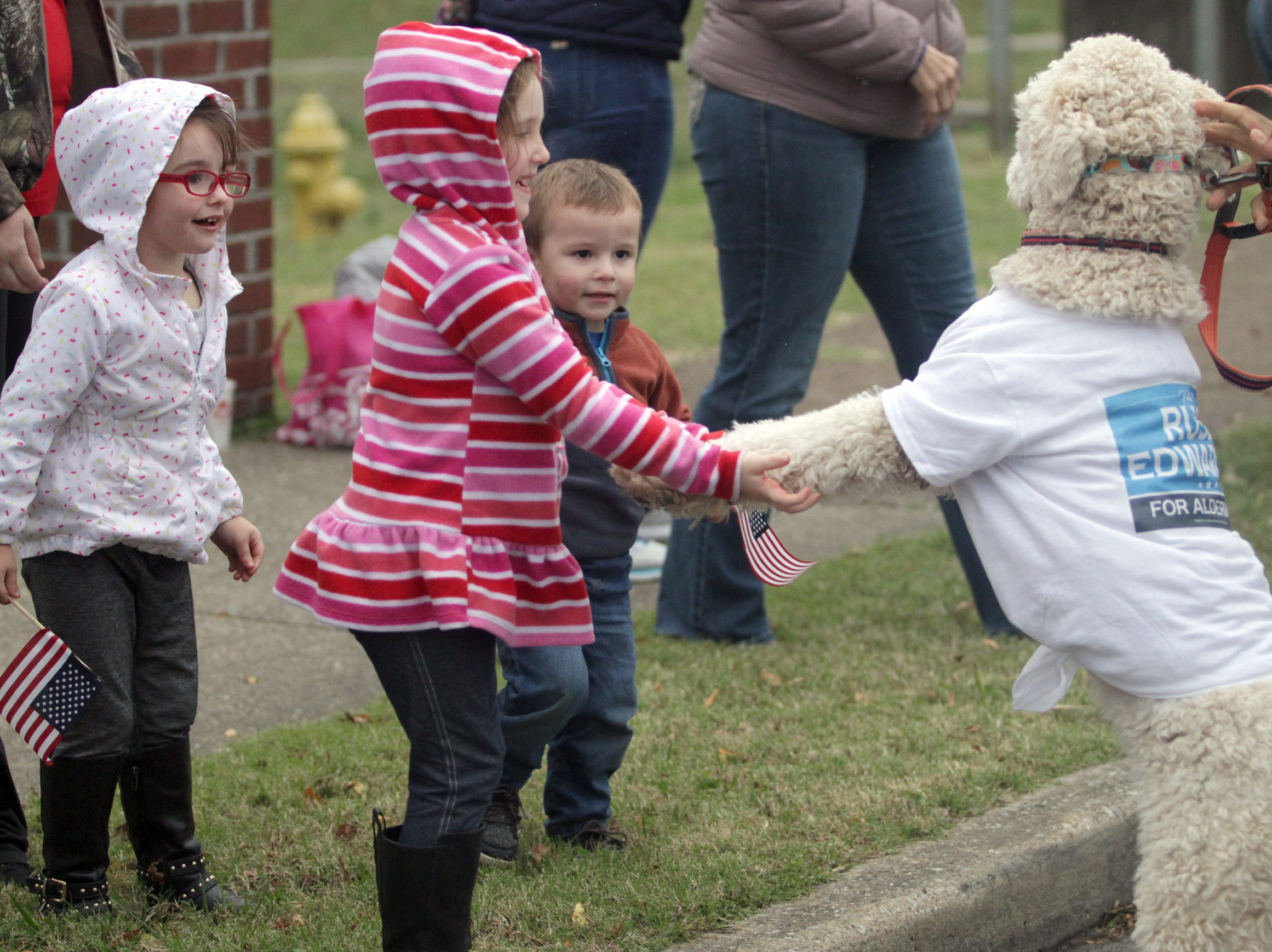 L-R Harmony (3) and Heaven (4) Voules greet a dog walking in the Veterans Day Parade in Hendersonville, TN on Sudnday, November 4, 2018.