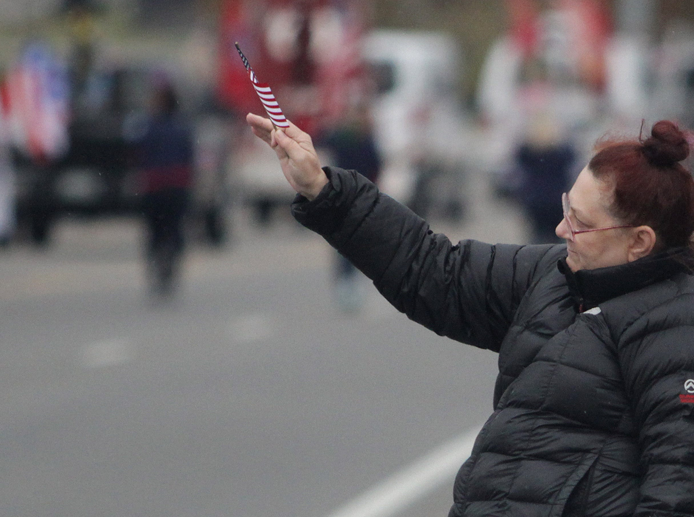 A woman waves her flag to the Vets riding in the Veterans Day Parade in Hendersonville, TN on Sunday, November 4, 2018.