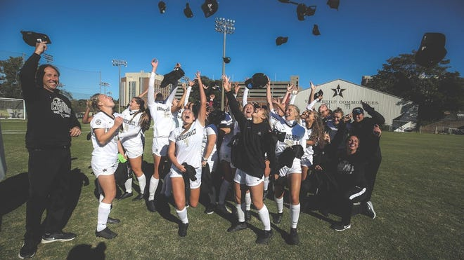 Vanderbilt women's soccer coach Darren Ambrose, left, and his players celebrate their SEC regular-season title.