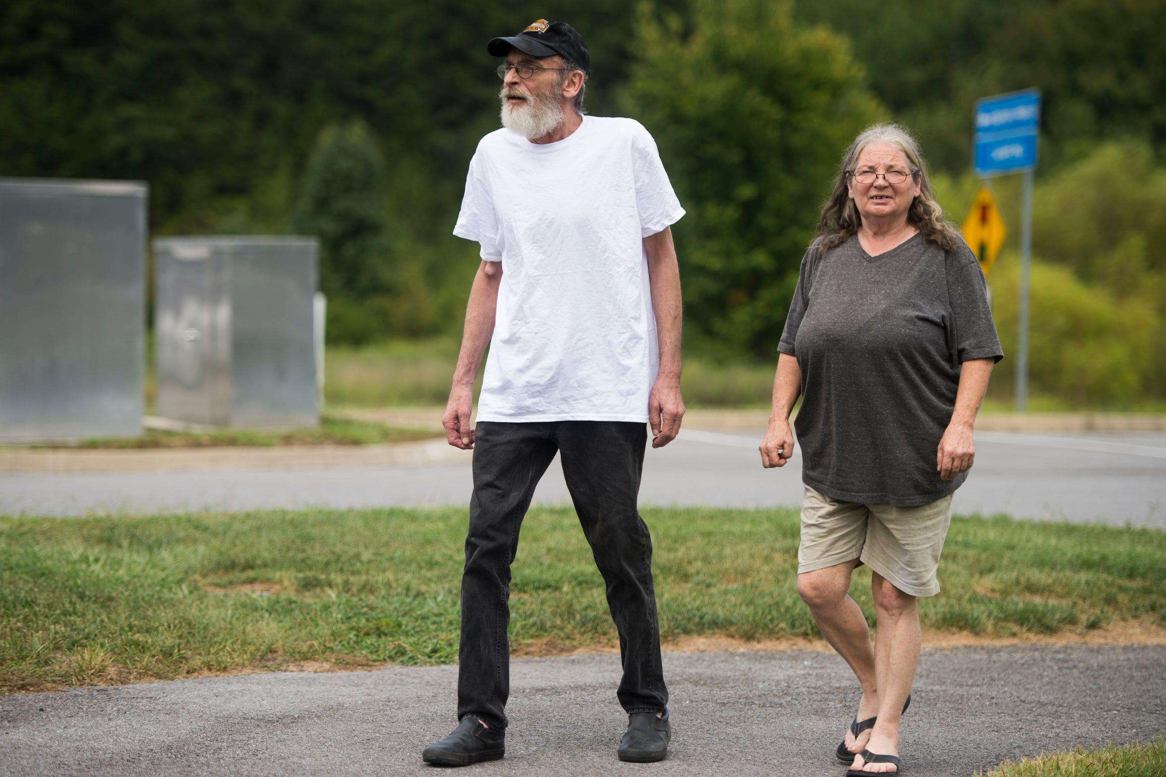 Alan Chrisman walks with his wife, Joyce, near the Sevierville, Tenn., McDonald's where he worked as a maintenance employee before being diagnosed with stage 4 colorectal cancer. Chrisman applied for disability but was initially denied based on a recommendation by a medical contractor hired by the state to review claims.
