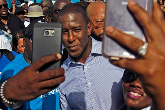 Democratic nominee for Florida governor Andrew Gillum, center, takes a moment for pictures with supporters before a rally in Miami on Sunday.