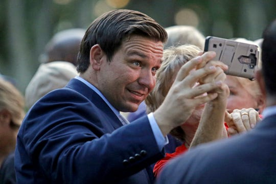 Republican Florida gubernatorial candidate Ron DeSantis takes a selfie with one of his supporters during a rally on Sunday in Boca Raton.