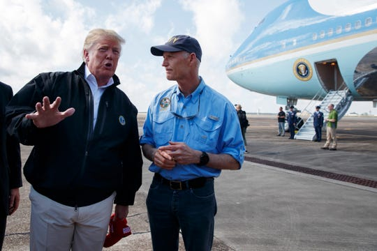 Florida Gov. Rick Scott listens to President Donald Trump on Oct. 15 at Eglin Air Force Base to visit areas affected by Hurricane Michael. Scott is challenging incumbent Democrat Sen. Bill Nelson.