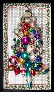 Creative sisters Denise Kluthe, of Naples, and Karen Elliott of Silver Spring, Maryland, attached vintage glass ornaments to a radiator screen to make a three-dimensional Christmas tree wall hanging.