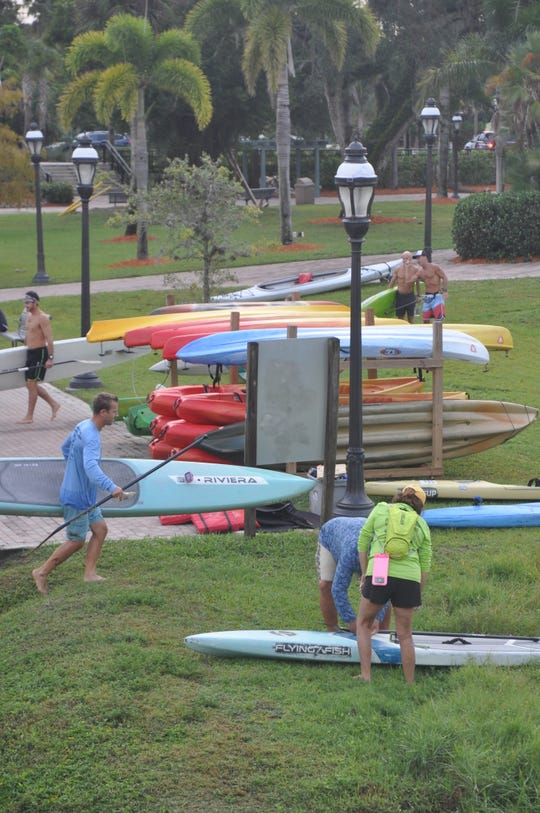 Racers get their paddleboards and kayaks ready for the race.