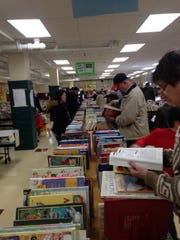 Thousands of books, most costing 50 cents to $4, line the tables at the College Club book sale in Ridgewood