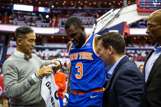 New York Knicks guard Tim Hardaway Jr. (3) is helped off court after falling during the first half of an NBA basketball game against the Washington Wizards, Sunday, Nov. 4, 2018, in Washington.