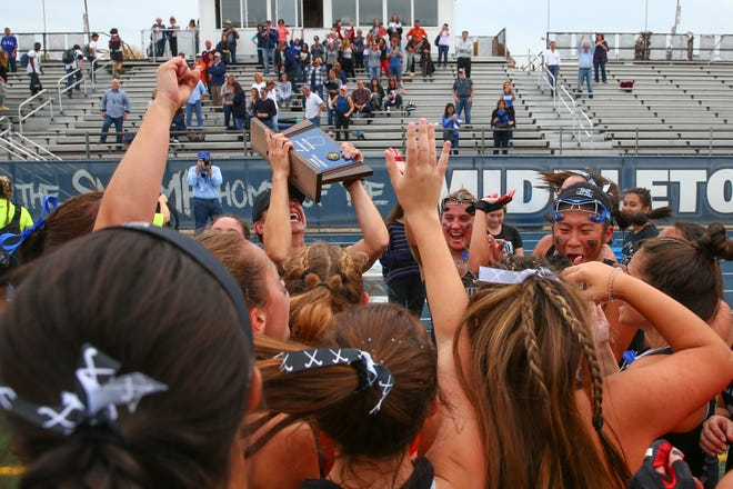 Millburn field hockey coach Sarah Pallino lifts the North 2, Group 3 sectional title trophy in the air in celebration.