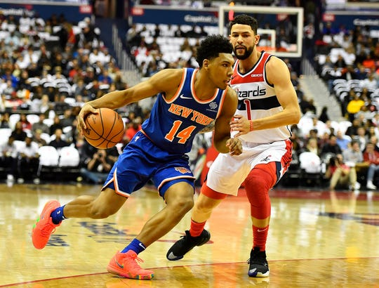 New York Knicks guard Allonzo Trier (14) dribbles past Washington Wizards guard Austin Rivers (1) during the first half at Capital One Arena.