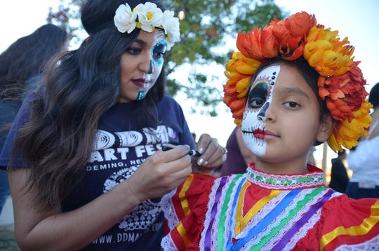 Volunteer Jessica Baeza paints half of 8-year-old Ella Baca's face.