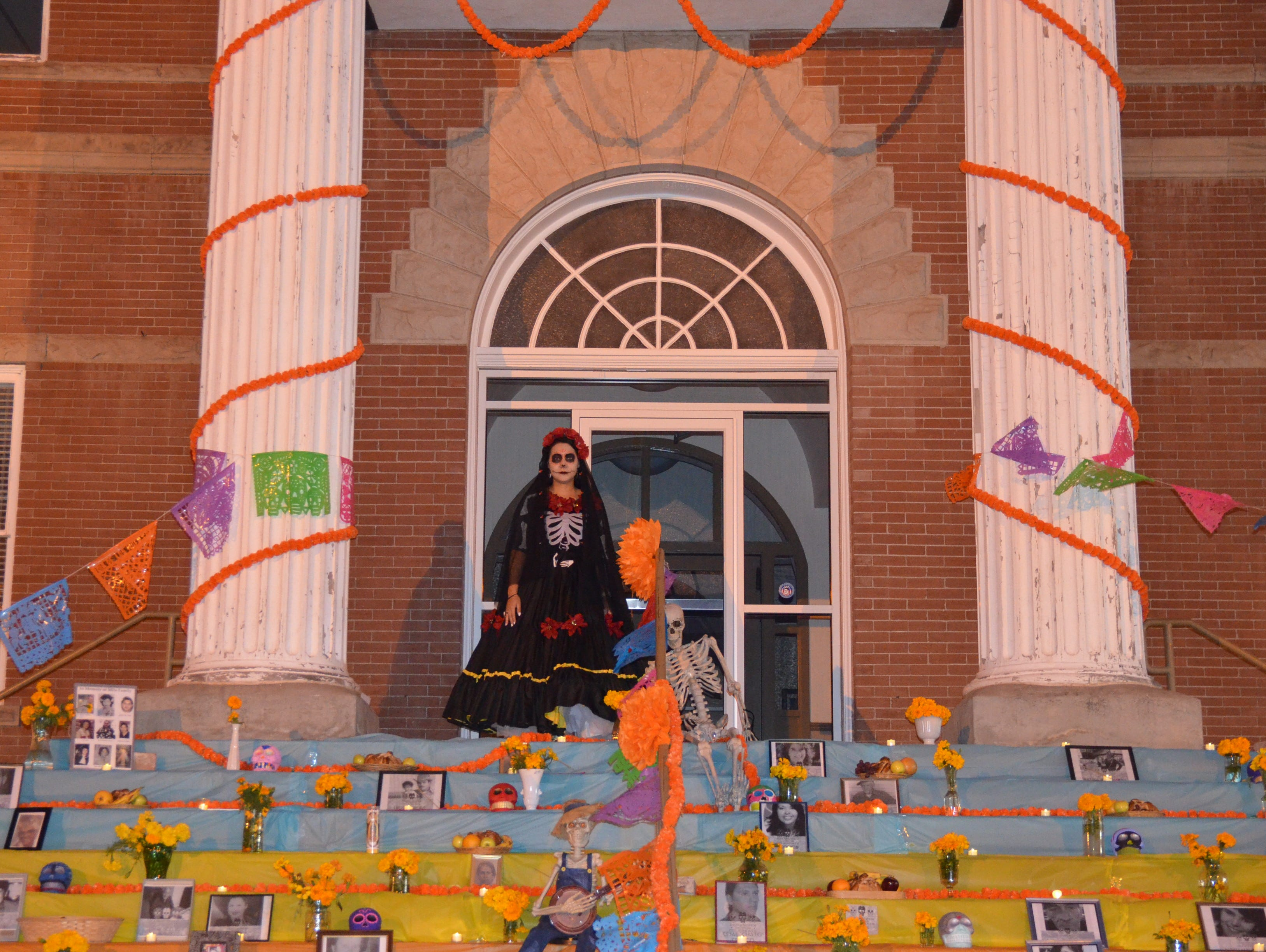 A Catrina Calavera stands on top of the Luna County Courthouse steps to oversee the Dia de los Muertos event.