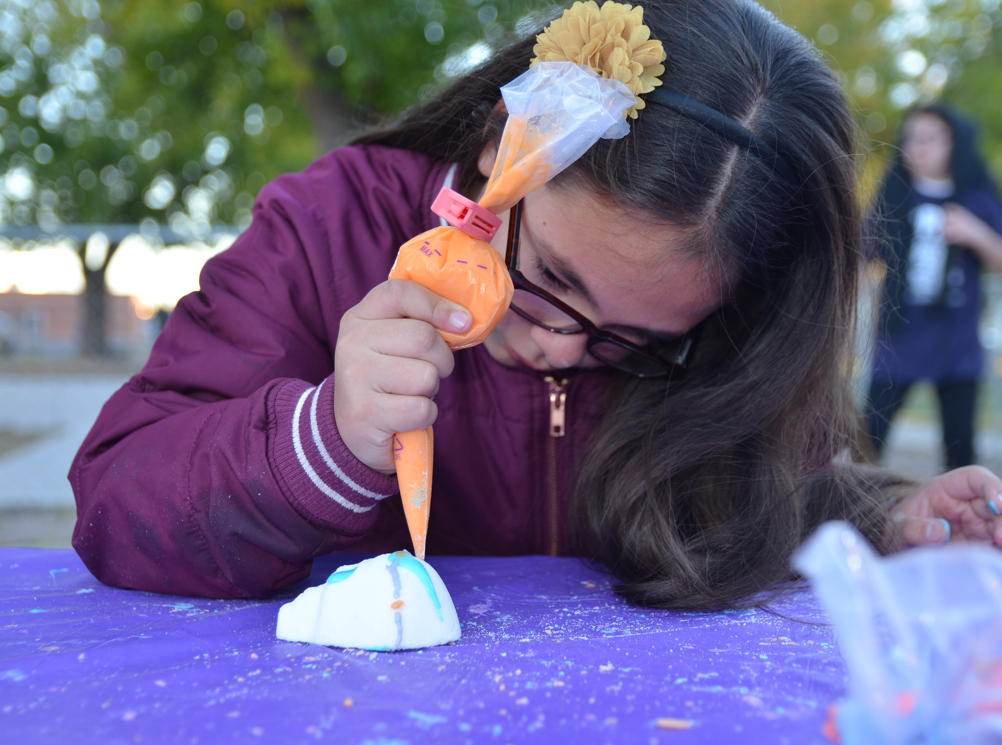 Aubree Garcia, 8, focuses in as she decorates her sugar skull.