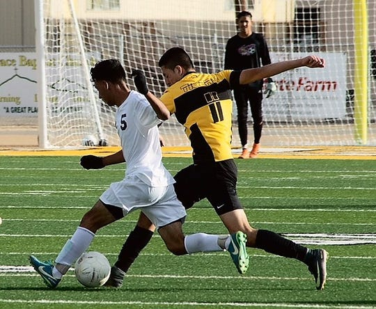 Alamogordo Tiger Julian Torres battles with Atrisco Heritage Academy Jaguar Eric Morales for control of the ball during first half play in their 5A playoff game Nov 3 at Riner Steinhoff Soccer Complex.  Torres would put up the the first score for both teams. At the break the score was knotted up at a one goal apiece. During the second half the Jaguars would score twice. At the final whistle the score would be Jaguars 3 - Tigers 1.