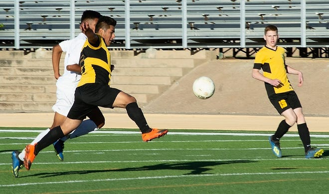 Alamogordo Tiger Rodolfo JR Barbosa attempts a goal during second half play.  Atrisco Heritage Academy Jaguar keeper Miguel Pedroza would grab the ball while it was still airborne, blocking the Tigers' attempt to get on the board during the second half of their 5A playoff game  Nov 3. at Riner Steinhoff Soccer Complex.  At the break the score was knotted up at one goal apiece. During the second half the Jaguars would score twice. At the final whistle the score would be Jaguars 3 - Tigers 1.