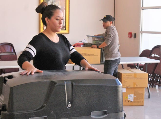 Monique Maynez moves a ballot box while Adam Baca prepares the computers at the Tays Center Monday. Voters have until 7 p.m. today, Nov. 6, to cast their vote in the midterm election.