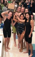 Northville swimmers hoist the championship trophy after winning the KLAA championship on Nov. 3 at Novi.