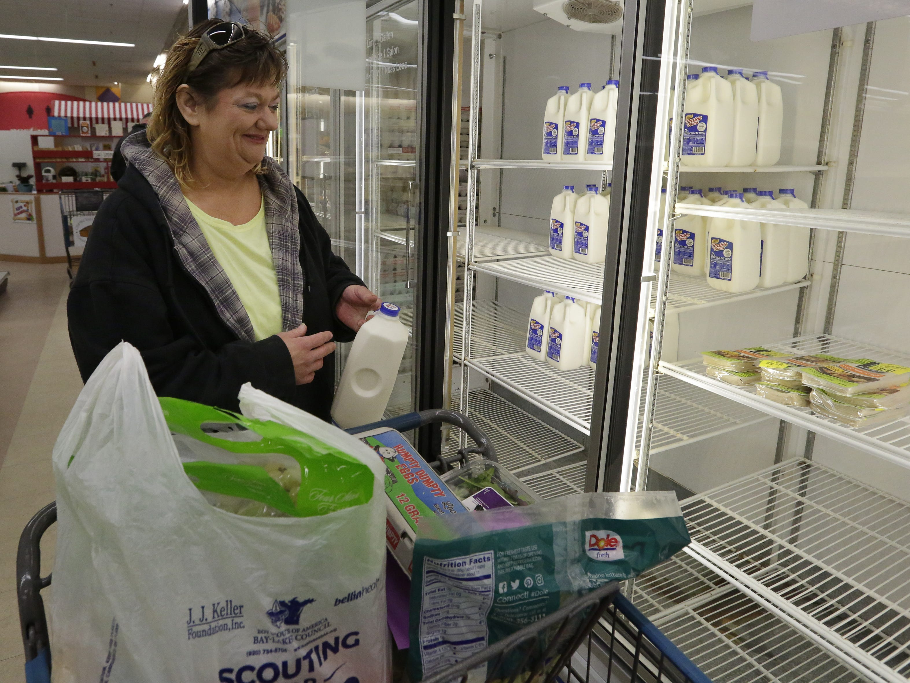 Donnette Collar takes milk from the cooler to put into her cart Thursday, Nov. 1, 2018, at the Oshkosh Area Community Pantry.