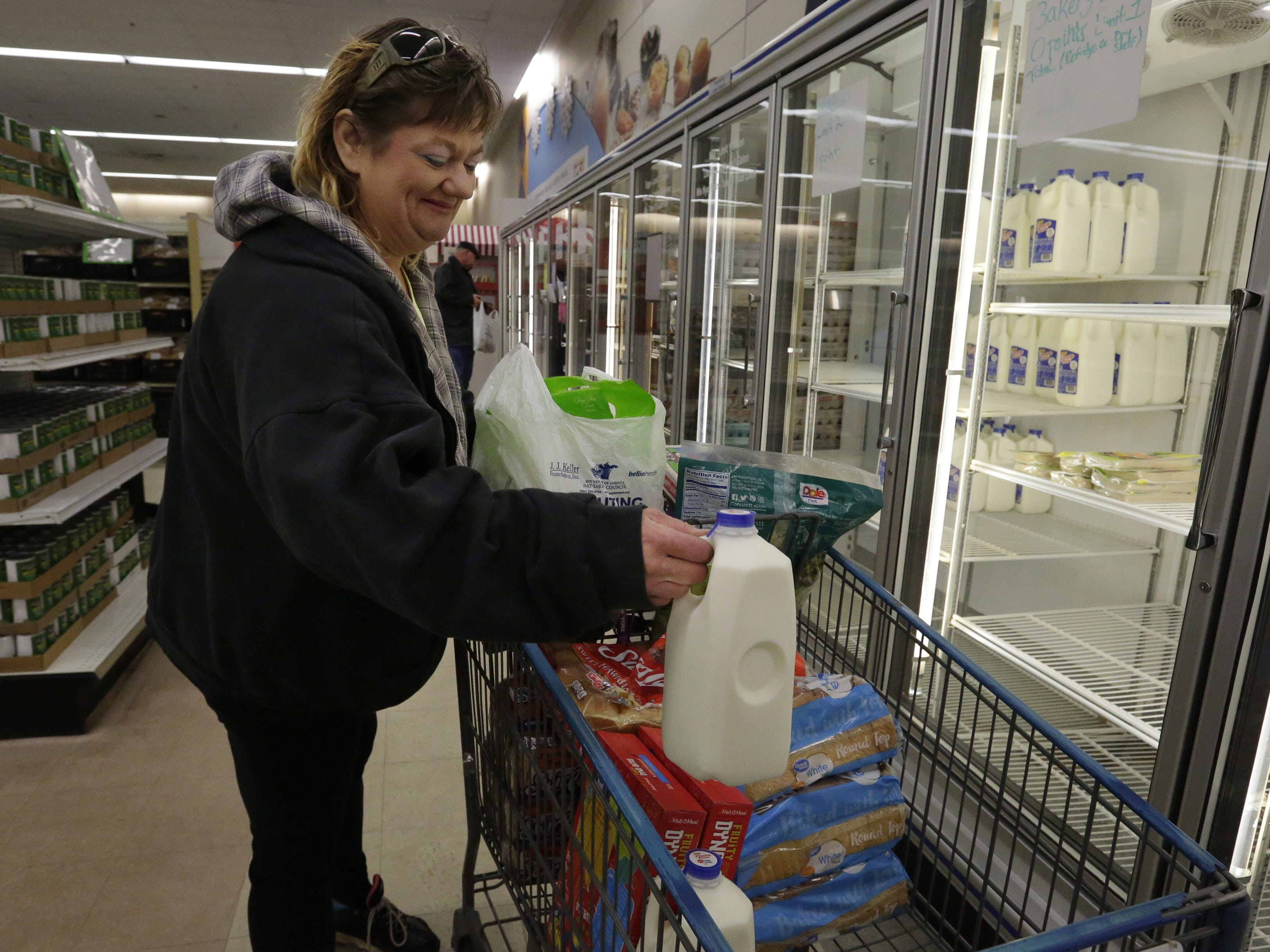 Donnette Collar takes milk from the cooler to put into her cart Thursday, Nov. 1, 2018 at the Oshkosh Area Community Pantry. The pantry has less than a hundred gallons of milk left as part of a shipment from The Emergency Food Assistance Program.