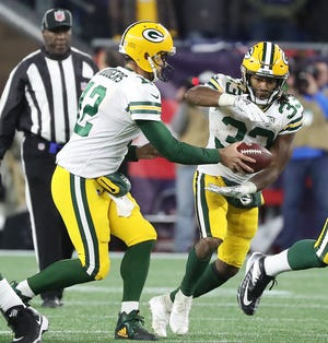 Green Bay Packers running back Aaron Jones (33) takes the hand off from quarterback Aaron Rodgers (12) against the New England Patriots Sunday, November 4, 2018 at Gillette Stadium in Foxborough, Mass.