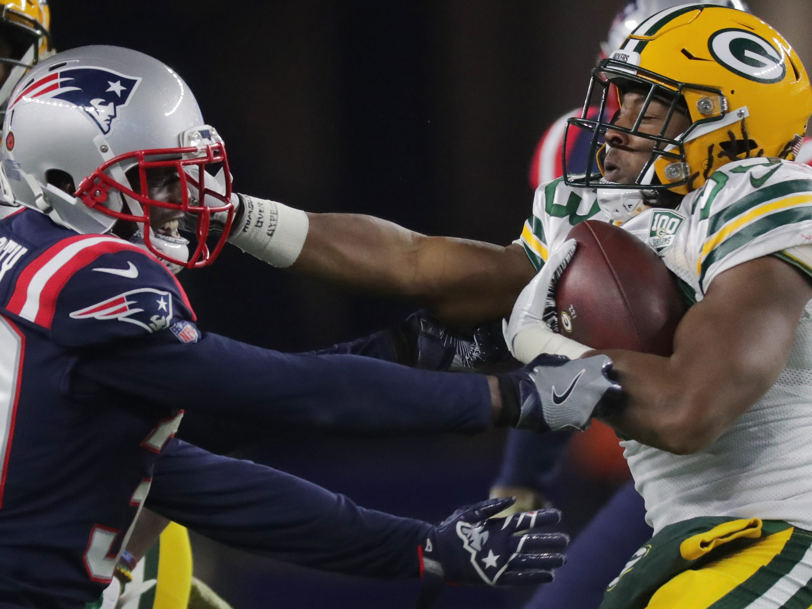 Green Bay Packers running back Aaron Jones (33) is tackled by New England Patriots cornerback Jason McCourty (30) after a short gain during the second quarter of their game Sunday, November 4, 2018 at Gillette Stadium in Foxborough, Mass.