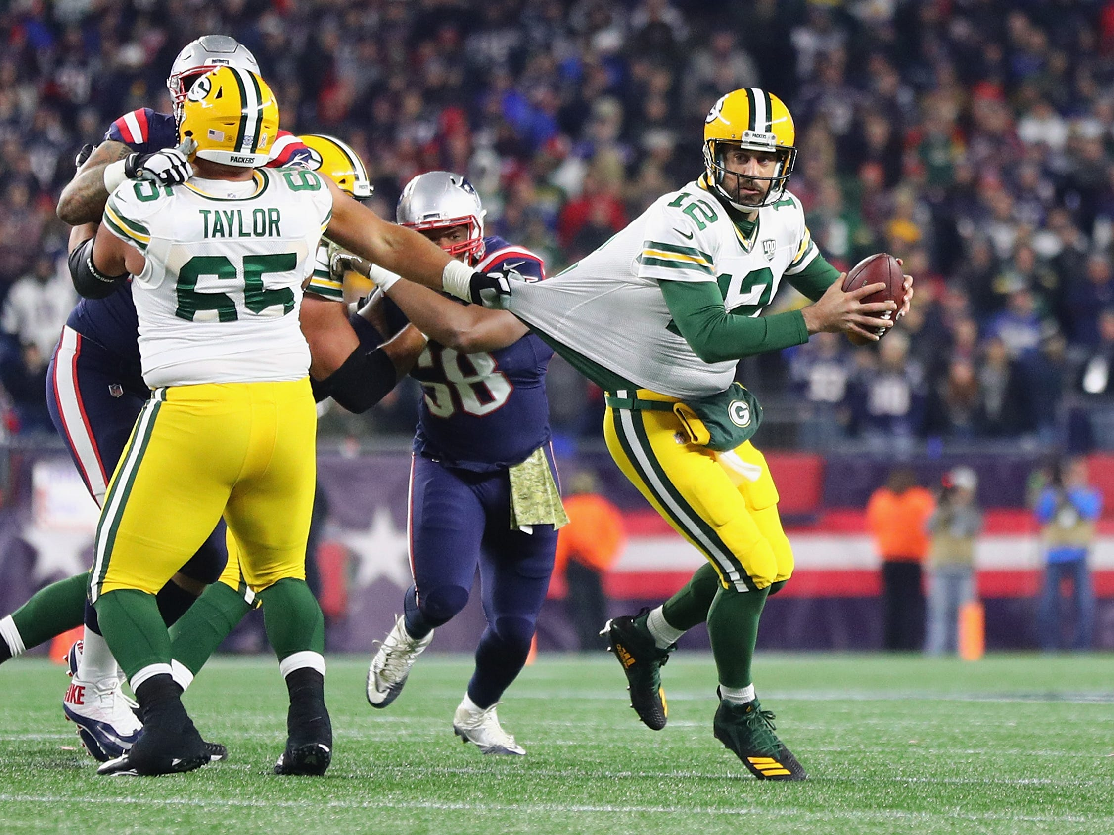 FOXBOROUGH, MA - NOVEMBER 04:  Aaron Rodgers #12 of the Green Bay Packers looks to pass the ball as his jersey is grabbed by Lawrence Guy #93 of the New England Patriots during the second half at Gillette Stadium on November 4, 2018 in Foxborough, Massachusetts.  (Photo by Maddie Meyer/Getty Images)
