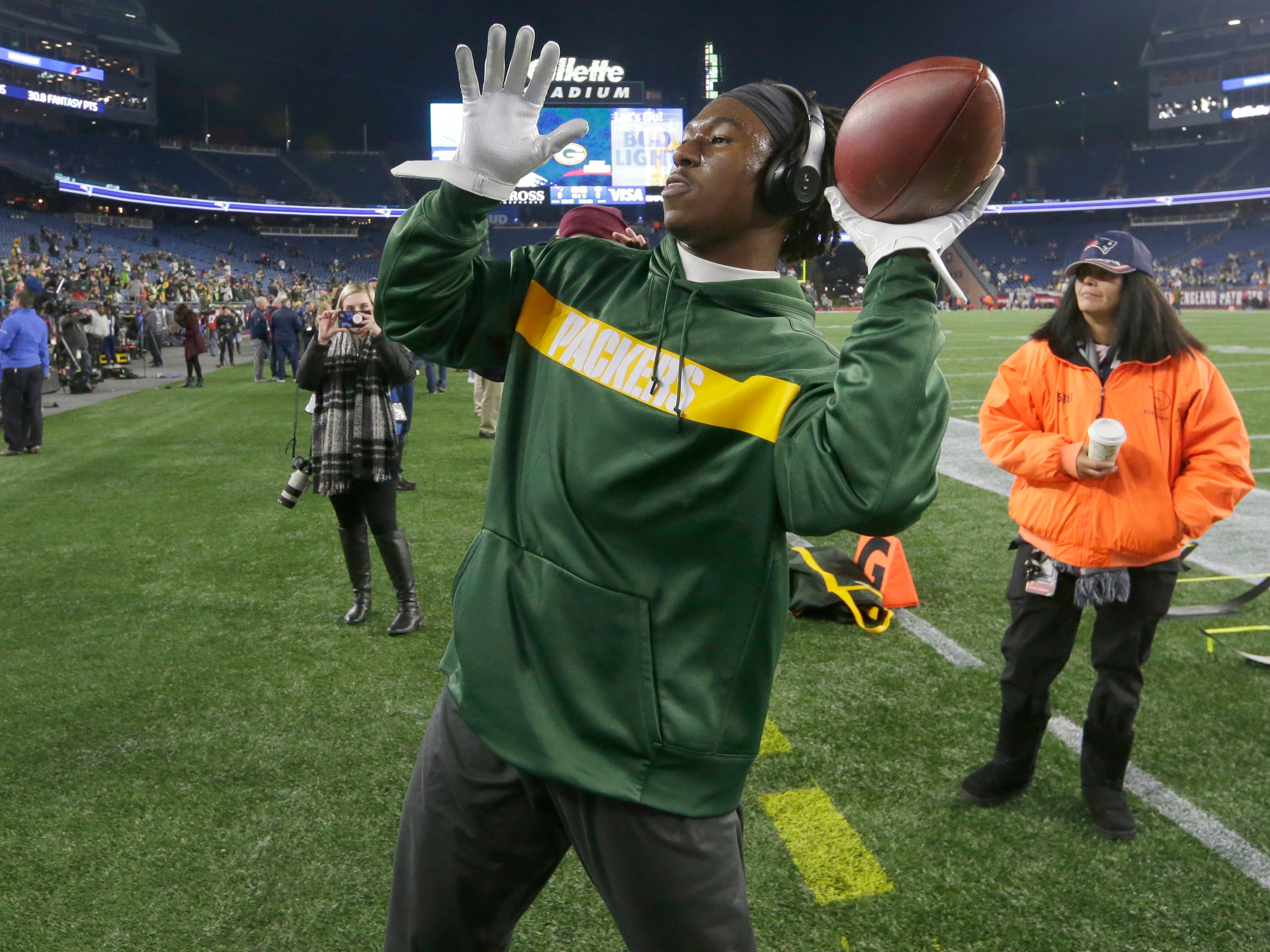 Green Bay Packers running back Jamaal Williams plays catch with a Packers fan in the stands before their game against the New England Patriots Sunday, November 4, 2018 at Gillette Stadium in Foxborough, Mass.