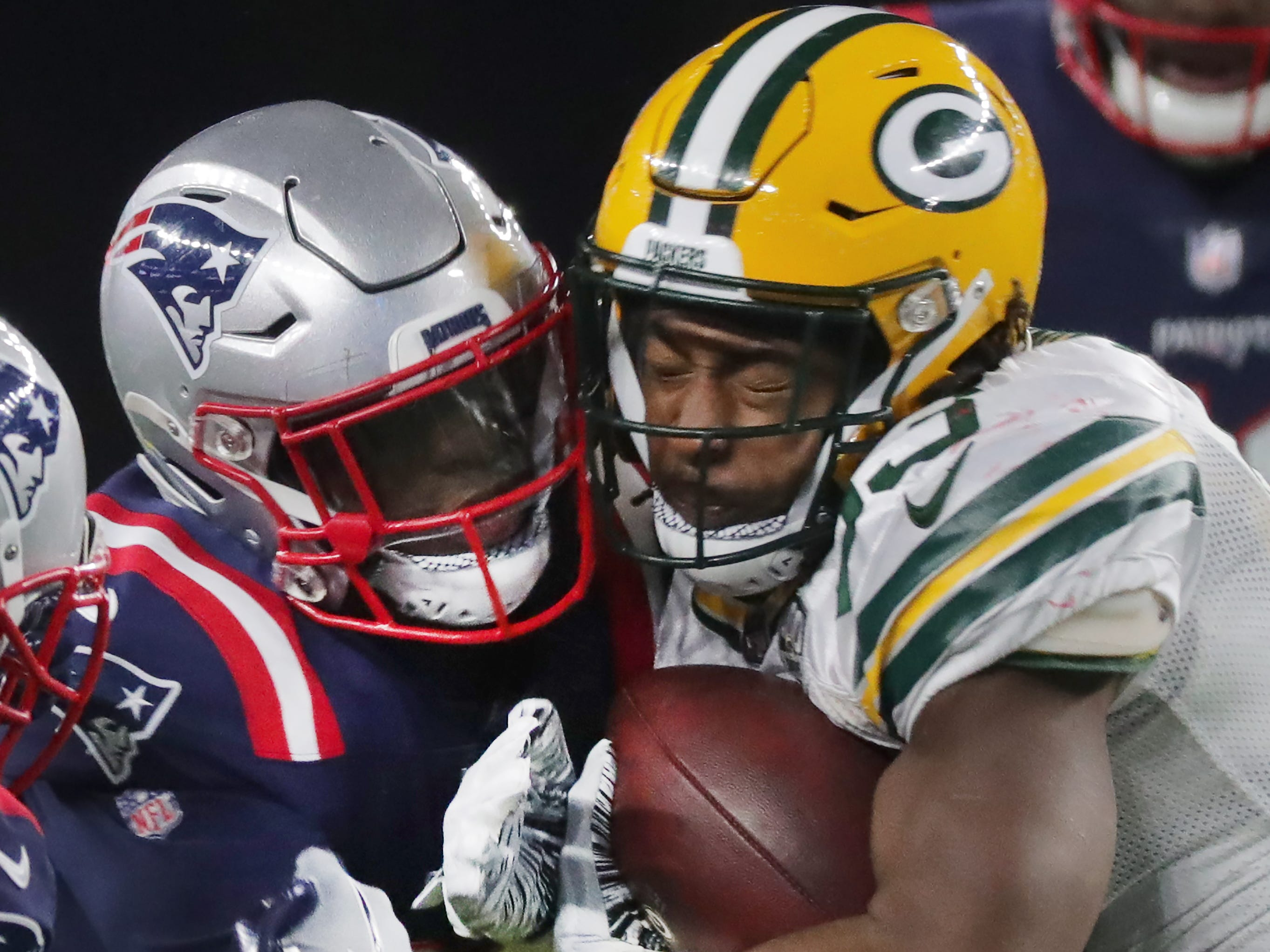 Green Bay Packers running back Aaron Jones (33) is hit by New England Patriots strong safety Duron Harmon (21) after short gain during the second quarter of their game Sunday, November 4, 2018 at Gillette Stadium in Foxborough, Mass.