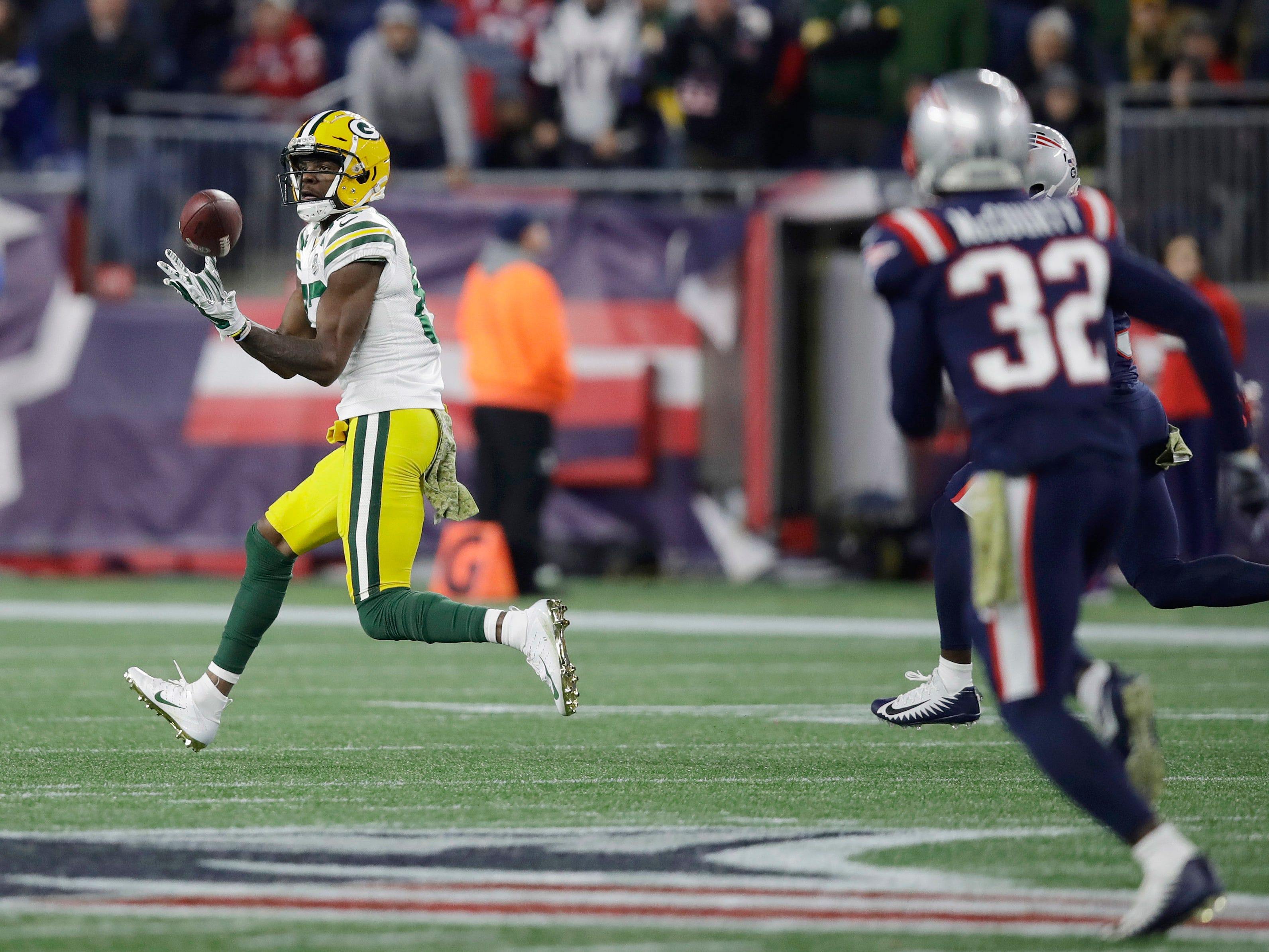 Green Bay Packers wide receiver Marquez Valdes-Scantling, left, catches a pass in front of New England Patriots defensive back Devin McCourty (32) during the second half of an NFL football game, Sunday, Nov. 4, 2018, in Foxborough, Mass. (AP Photo/Charles Krupa)