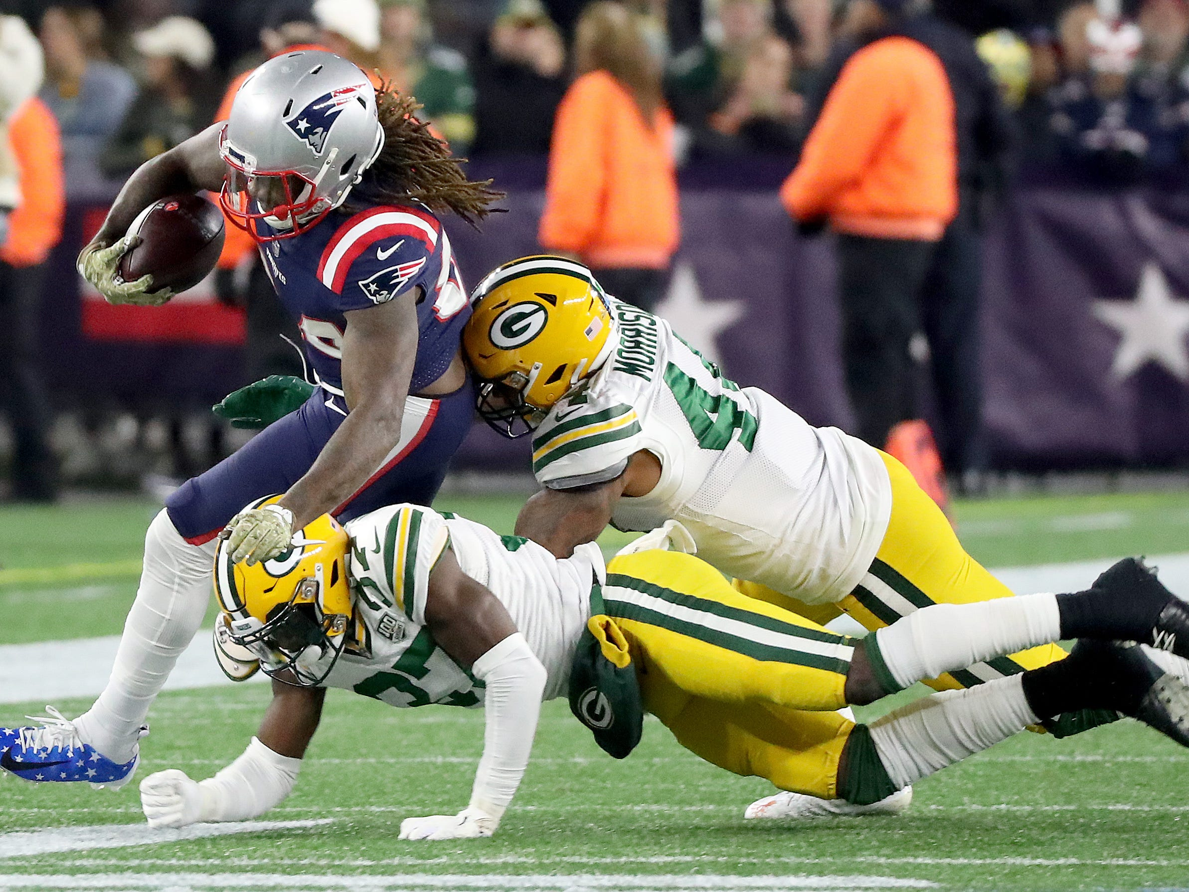 Green Bay Packers cornerback Josh Jackson (37) and inside linebacker Antonio Morrison (44) tackle wide receiver Cordarrelle Patterson (84) against the New England Patriots Sunday, November 4, 2018 at Gillette Stadium in Foxborough, Mass.
