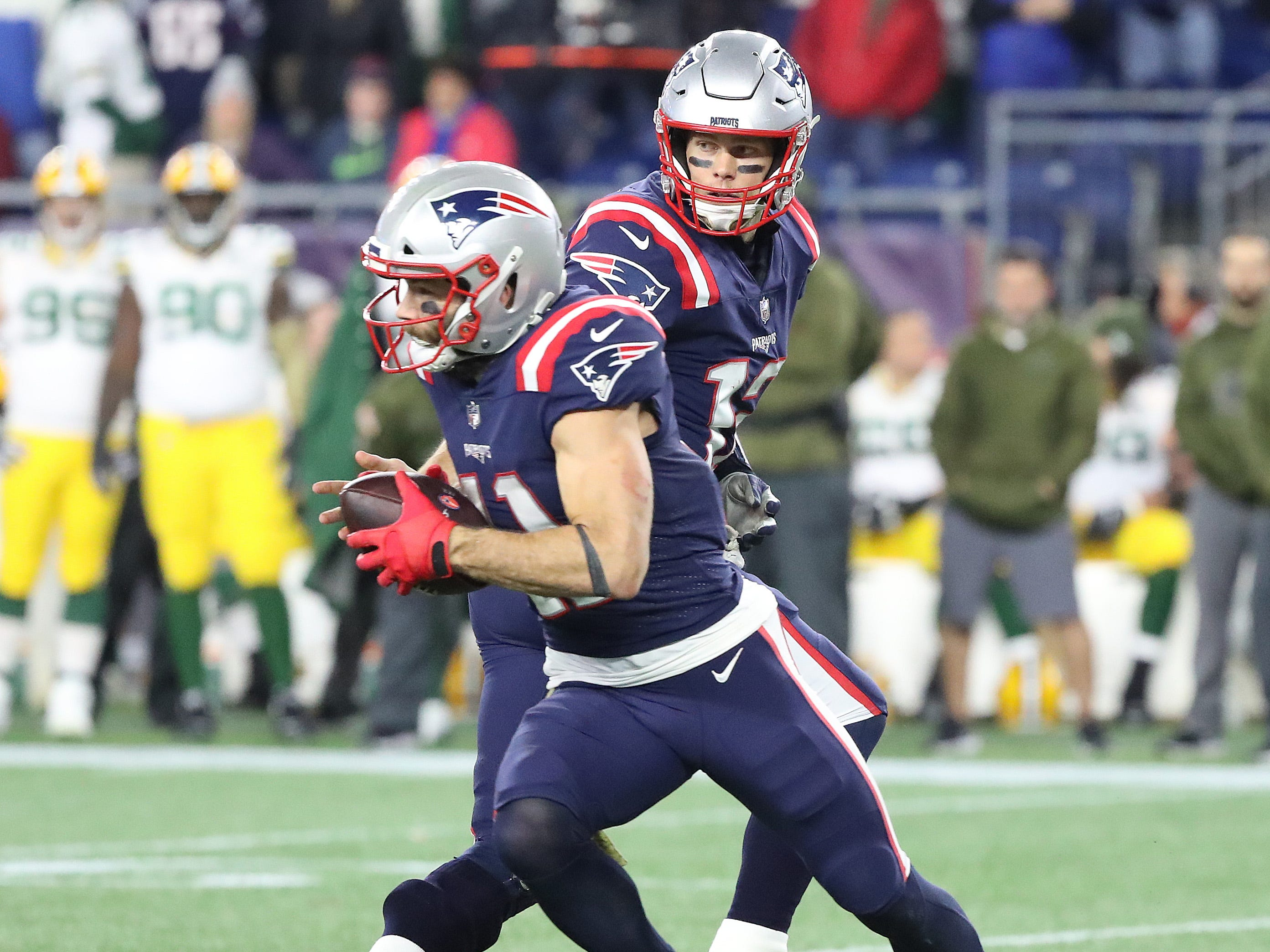 New England Patriots quarterback Tom Brady (12) hands off to wide receiver Julian Edelman (11) against the Green Bay Packers Sunday, November 4, 2018 at Gillette Stadium in Foxborough, Mass.