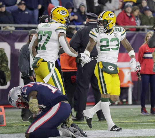 Green Bay Packers cornerback Jaire Alexander (23) and defensive back Josh Jones (27) celebrate a stop against the New England Patriots Sunday, November 4, 2018 at Gillette Stadium in Foxborough, Mass.