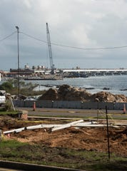Crews work on demolishing the Five Flags Memorial Park at the foot of the Pensacola Bay Bridge on Monday.