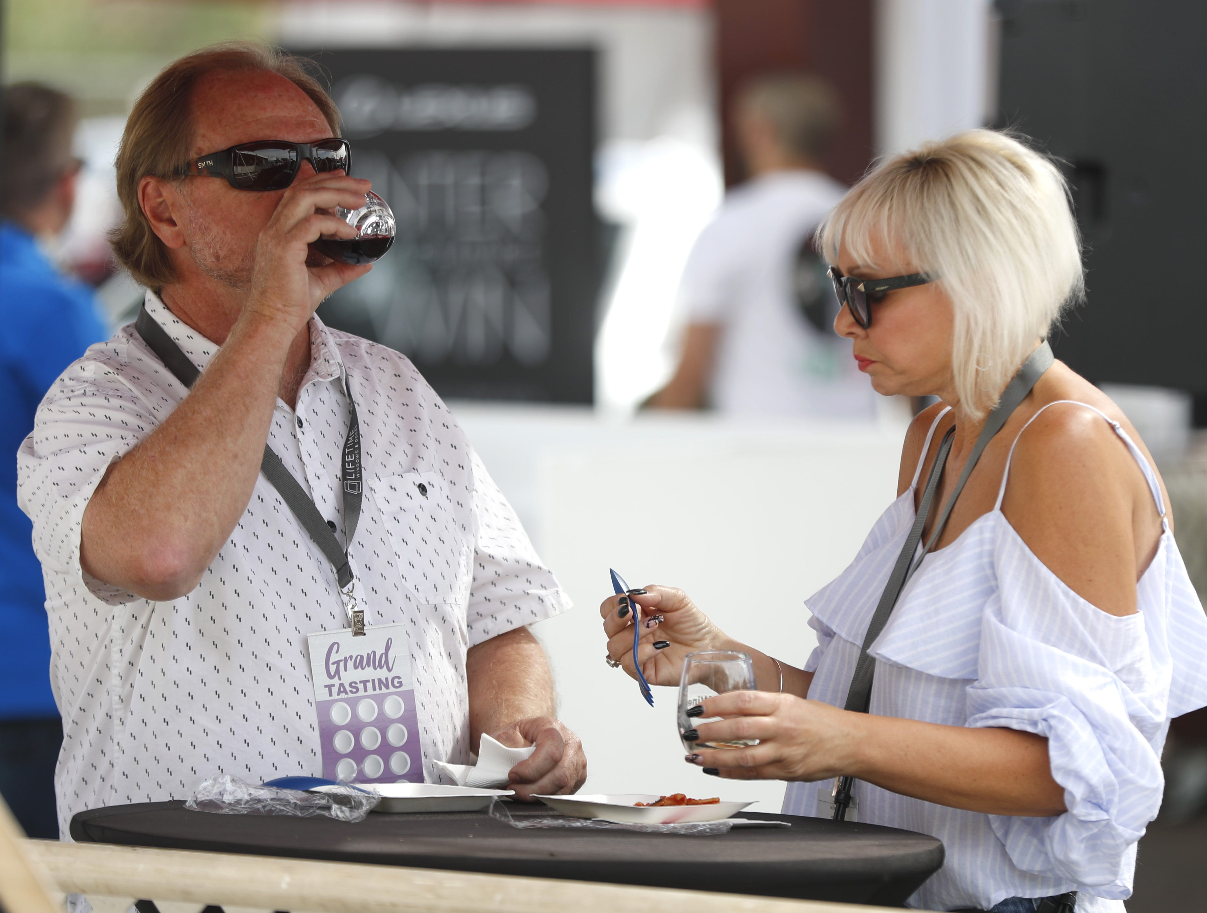 People take a moment to taste their wine and food during the azcentral Wine & Food Experience at WestWorld of Scottsdale, Ariz. on Nov. 4, 2018.