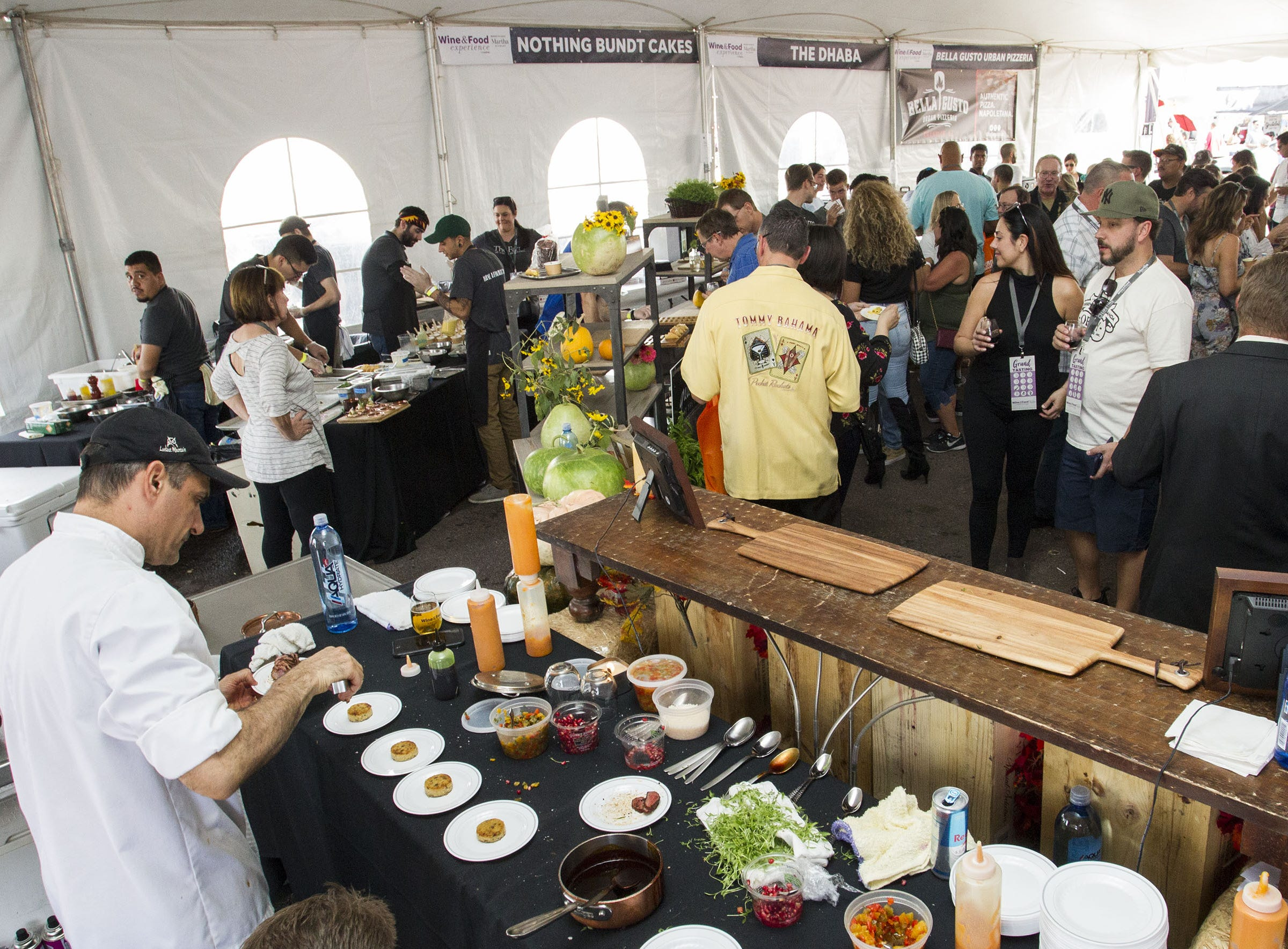 Food is prepared as Wine & Food lovers wait for samples during the azcentral Wine & Food Experience at WestWorld of Scottsdale, Sunday, Nov. 4, 2018.