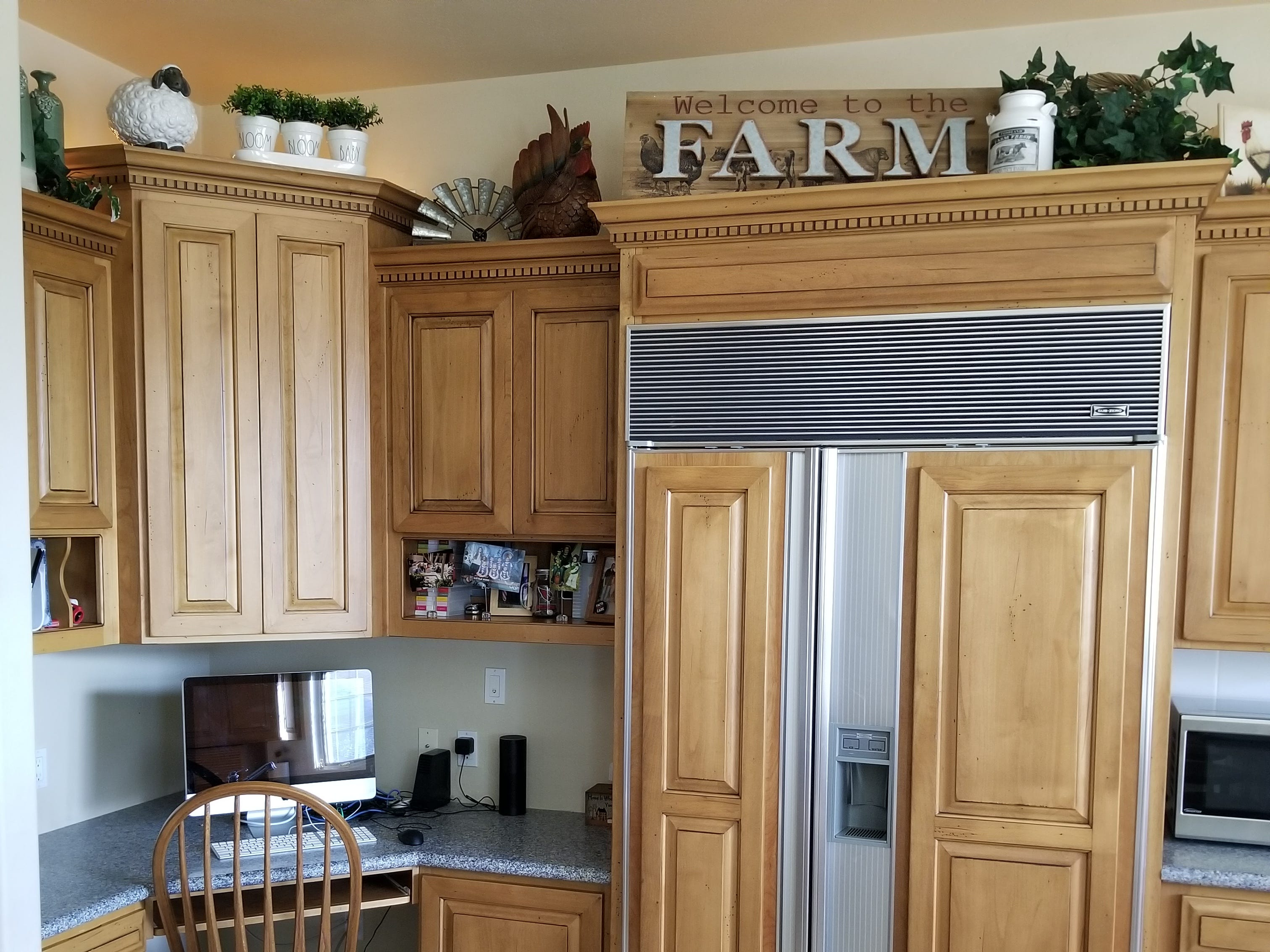 Sub-Zero refrigerator with cabinetry panels and corner desk opposite the pantry lend to a quick recipe find or checking on the sheep via a camera link to the barn.