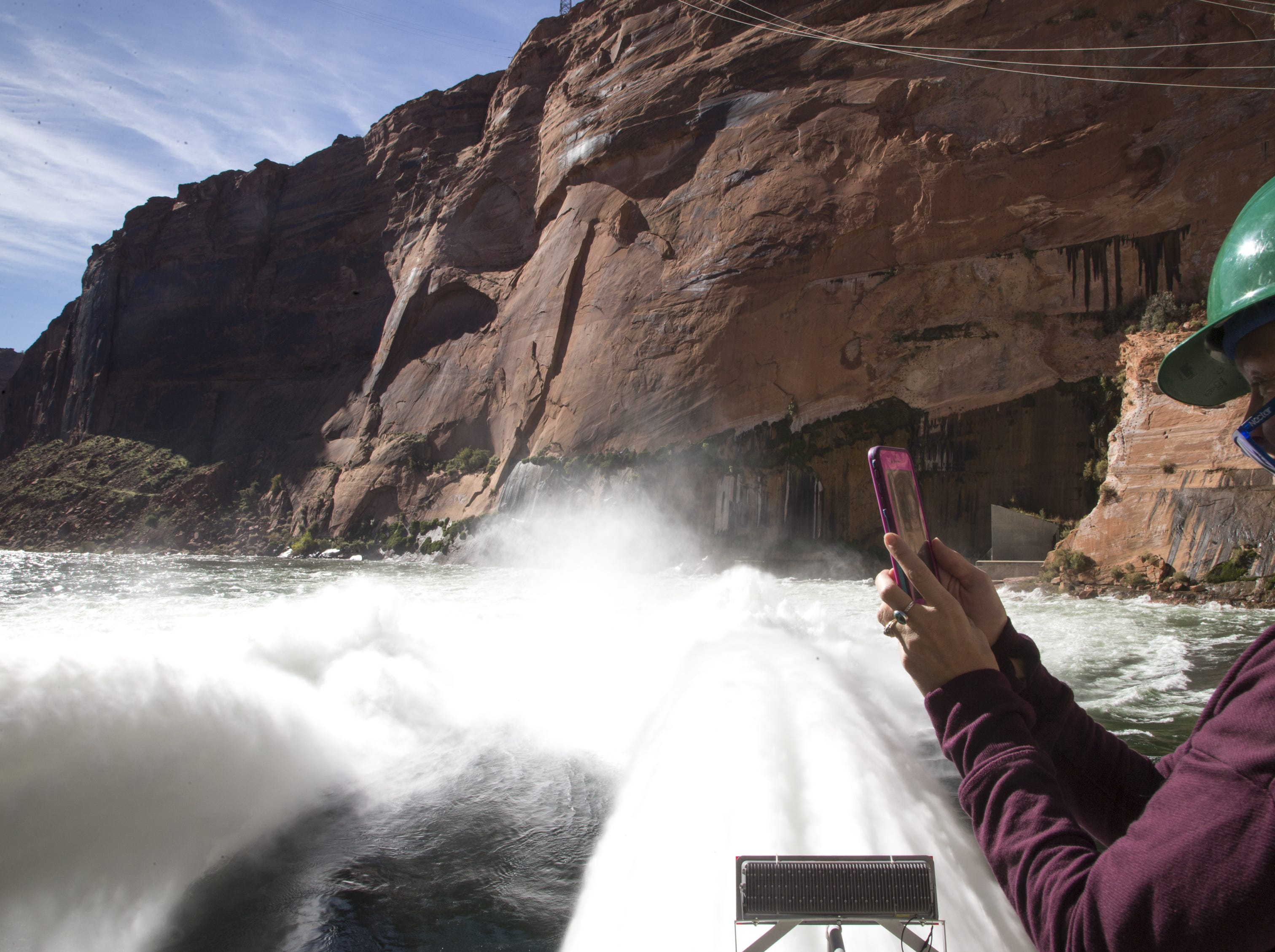 Emily Omana Smith takes a video of water being released from Glen Canyon Dam through a bypass tube Nov. 5, 2018, during a high-flow experiment.