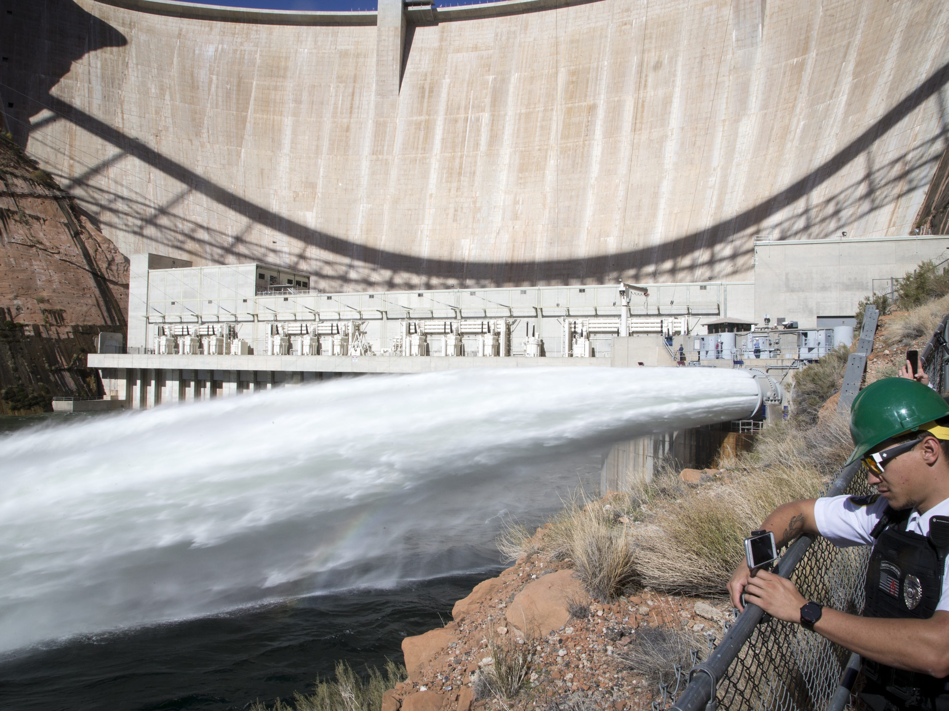 Skyler Emmons takes a video of water being released from Glen Canyon Dam through a bypass tube on Nov. 5, 2018, during a high-flow experiment.