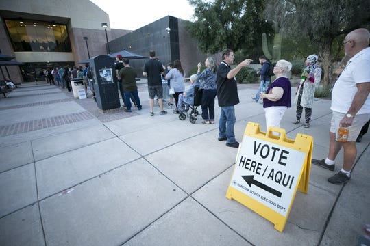 People wait in line to vote for the primary, at the polling place at the Tempe Public Library on Tuesday evening, August 28, 2018. People leave the polling place said they waited in line for two hours.