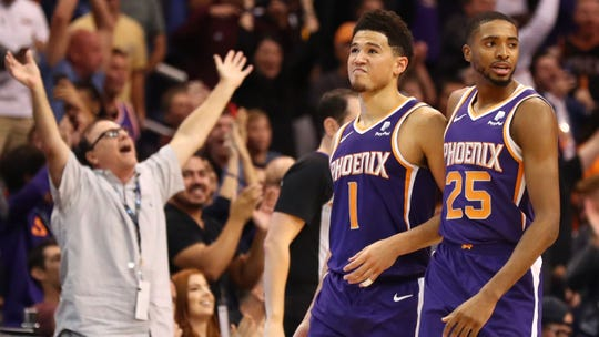Phoenix Suns' Mikal Bridges and Devin Booker celebrate late in Sunday's 102-100 win over Memphis