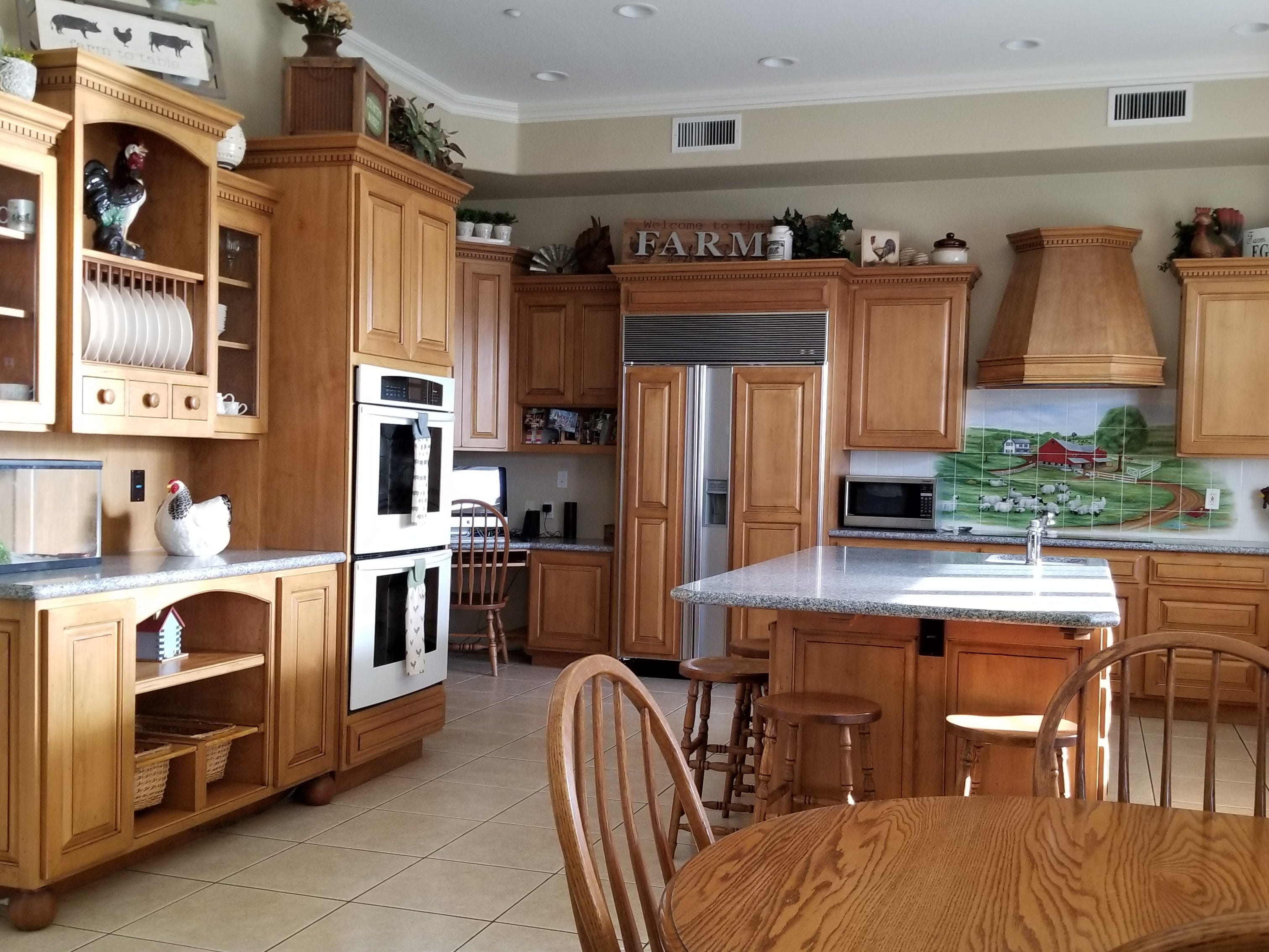 Double ovens and a built-in hutch provide ample storage since the family opted for an office vs. a dedicated dining room.  Bar stools add additional seating. Farm accents throughout the home bring to bear the ever present love for farm life.