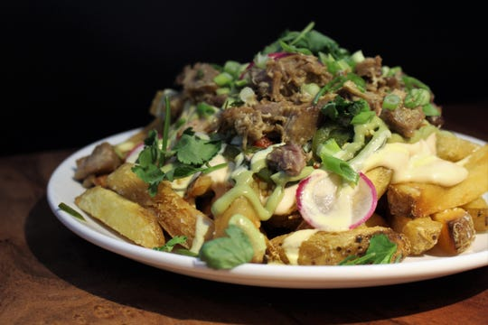 The lunch menu at Normal Restaurant includes Normal Fries made with Frites Street thick-cut fries buried under cheese sauce, carnitas, chiles, avocado salsa and corn aioli.